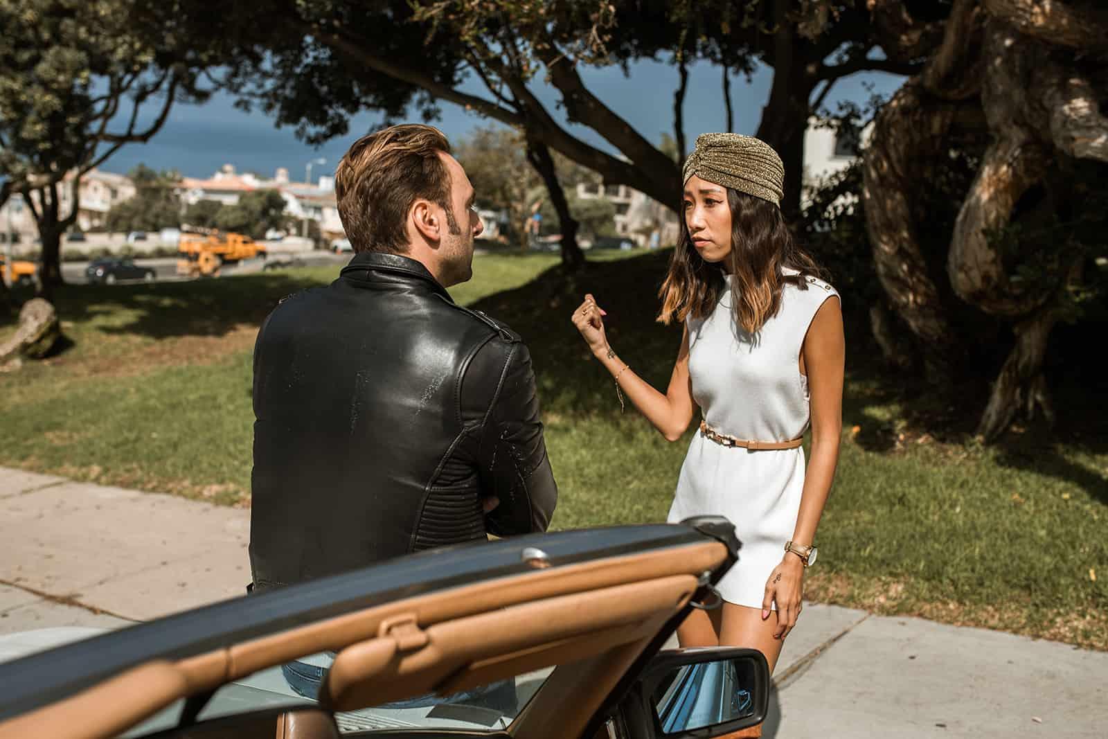 eine eifersüchtige Frau, die mit einem Freund spricht, der sich auf ein Auto auf der Straße stützt