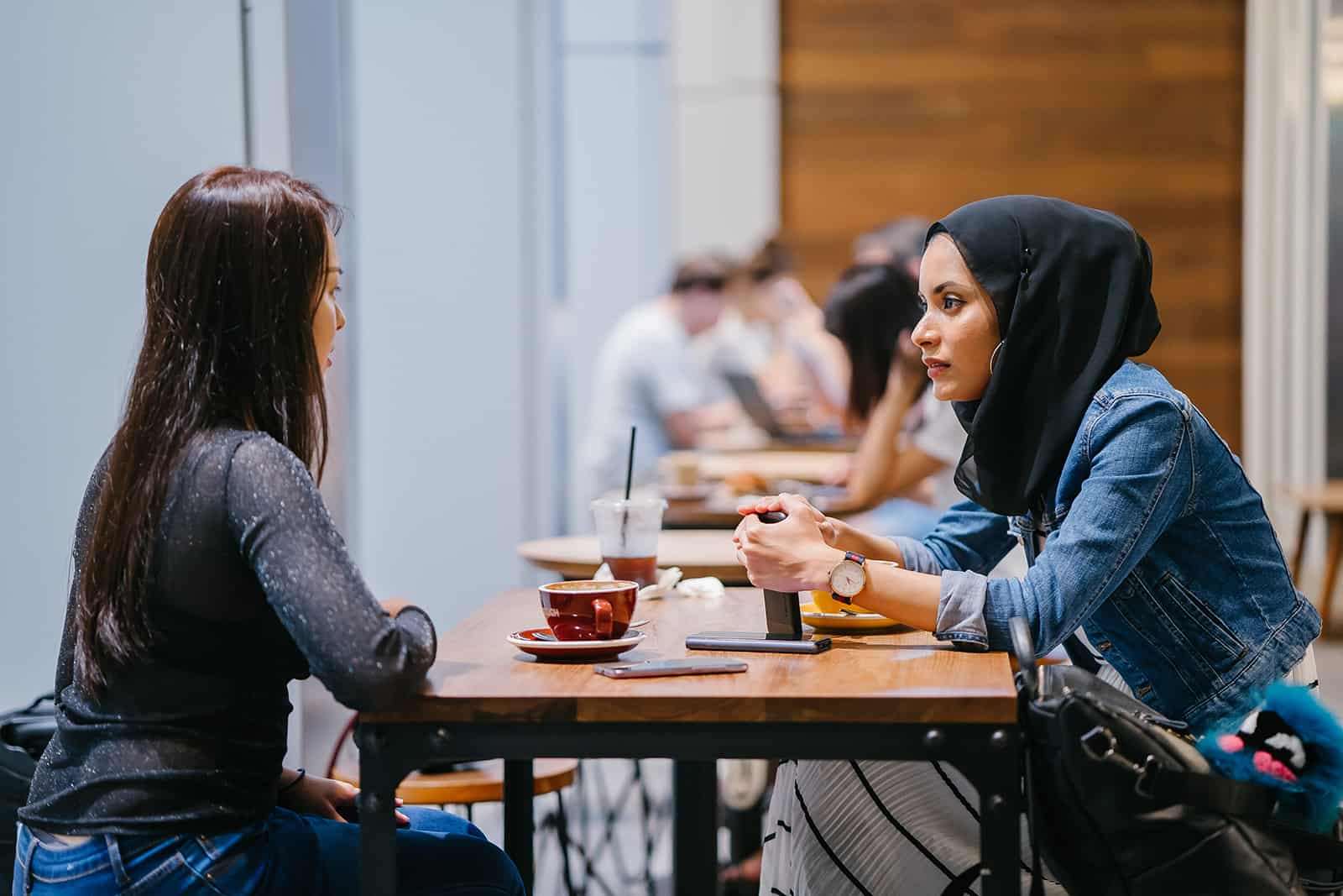 eine enttäuschte Frau, die ihre Freundin ansieht, die ihr im Café gegenüber sitzt