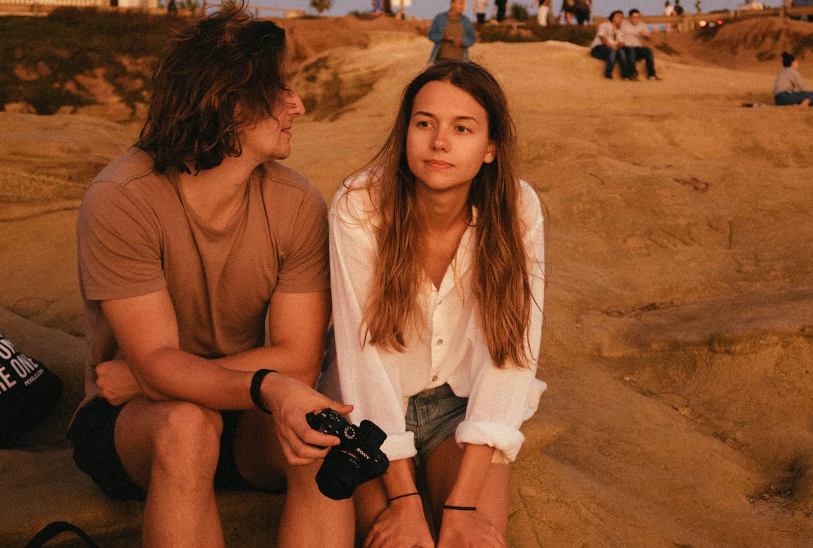 eine ernste Frau sitzt auf einem Felsen mit einem Mann, der sie ansieht