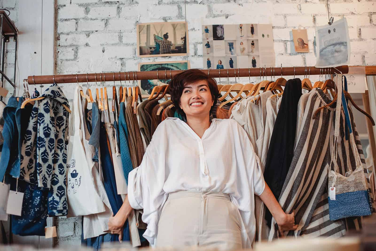 eine fröhliche Frau, die in einem Kleidergeschäft steht und Kleidung auf dem Gestell berührt