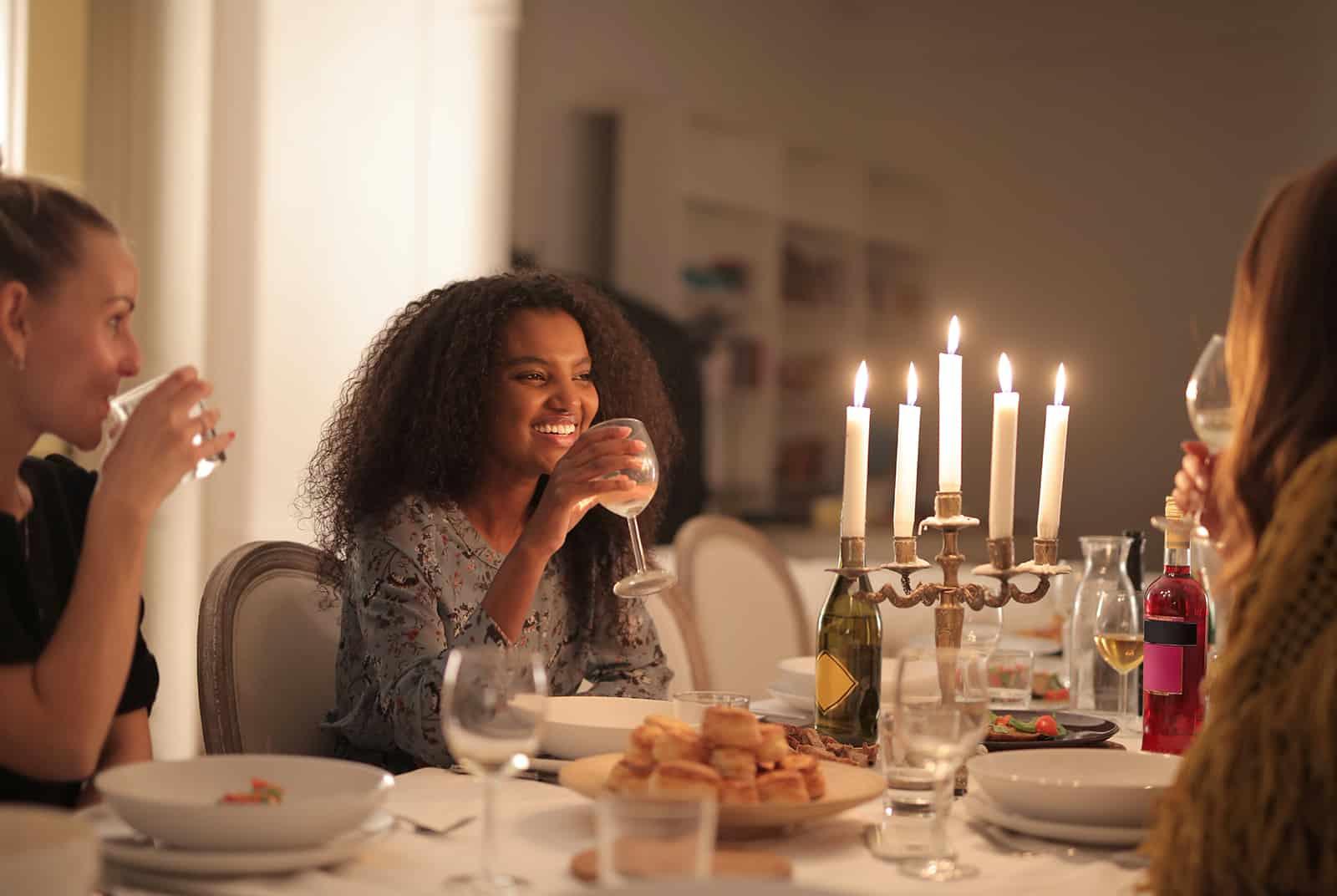 eine fröhliche Frau, die ein Glas Wein bei einem Abendessen mit Freunden hält