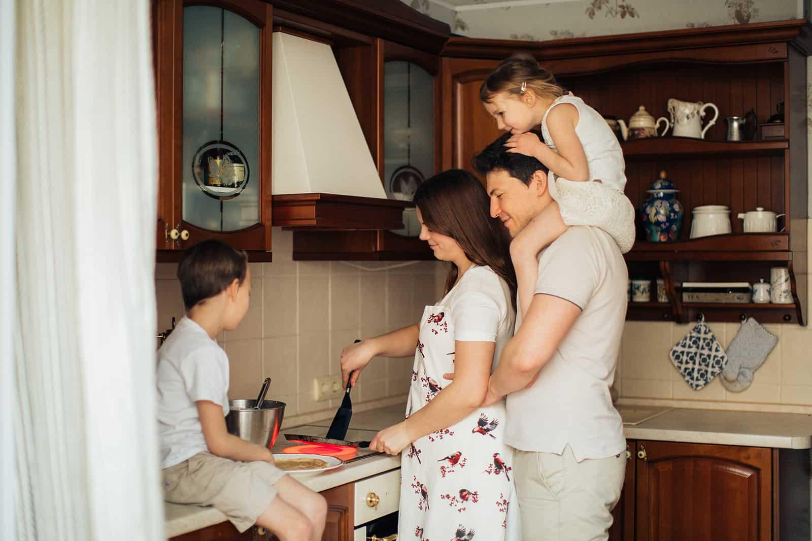 eine glückliche Familie, die Pfannkuchen in der Küche zubereitet