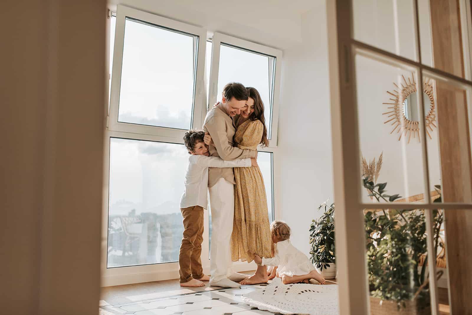 eine glückliche Familie, die sich am Fenster umarmt