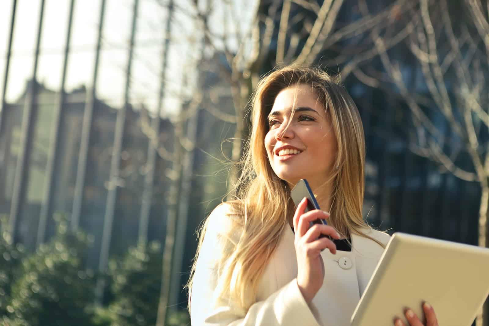 eine lächelnde Frau, die beiseite schaut, während sie das Telefon und das Tablett draußen hält