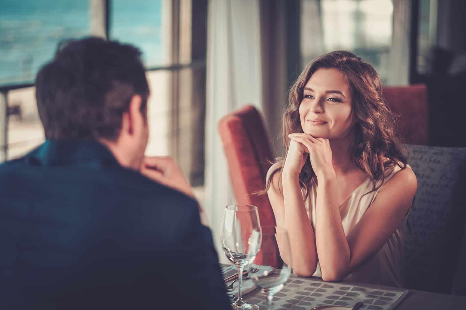 eine lächelnde Frau, die das Kinn auf ihre Hände stützt und auf einen Mann schaut, der mit ihr in einem Restaurant sitzt