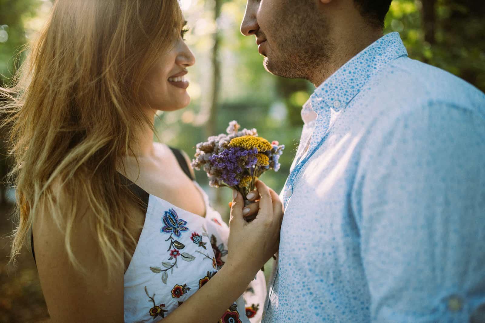 eine lächelnde Frau, die einen Blumenstrauß vor einem Mann hält, der nahe bei ihr steht