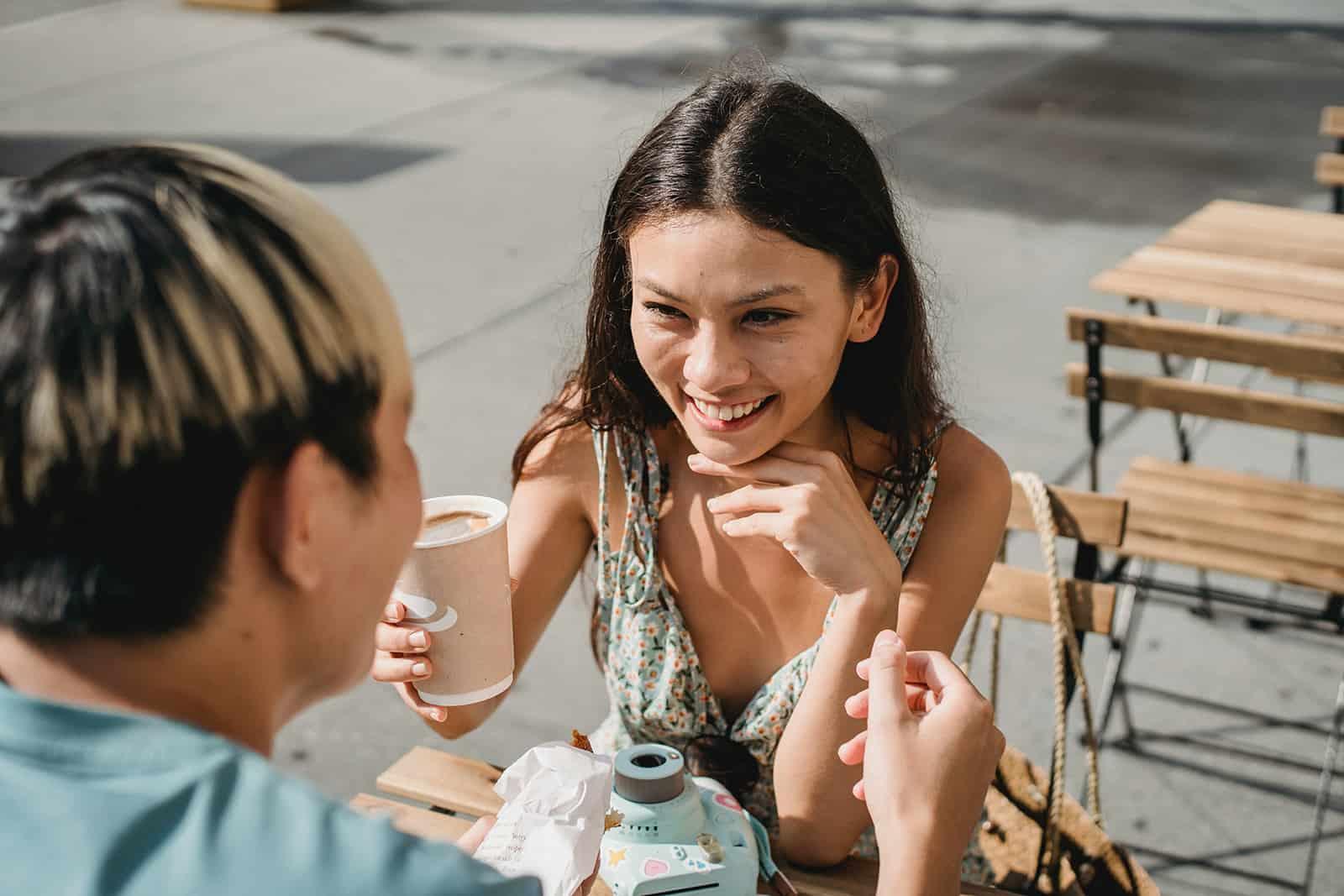 eine lächelnde Frau, die einen Kaffee hält, der mit einem Mann im Café sitzt