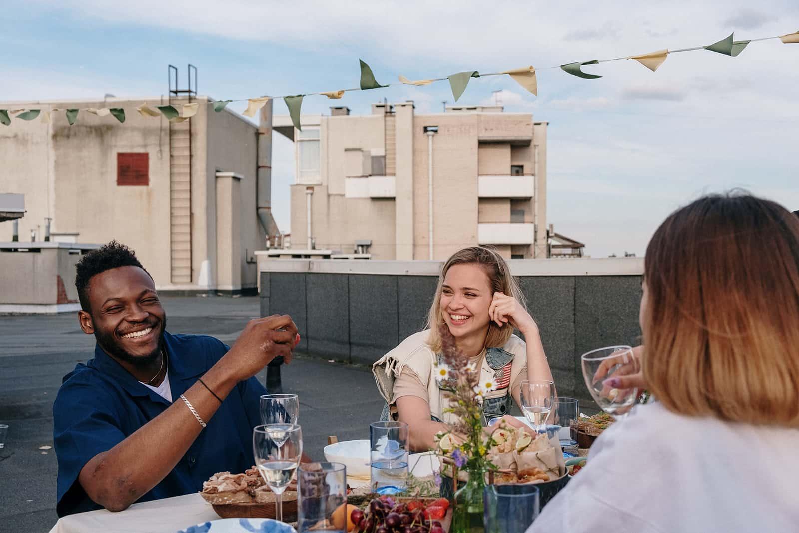 eine lächelnde Frau, die einen lächelnden Mann betrachtet, der mit Freunden auf dem Dach am Tisch sitzt