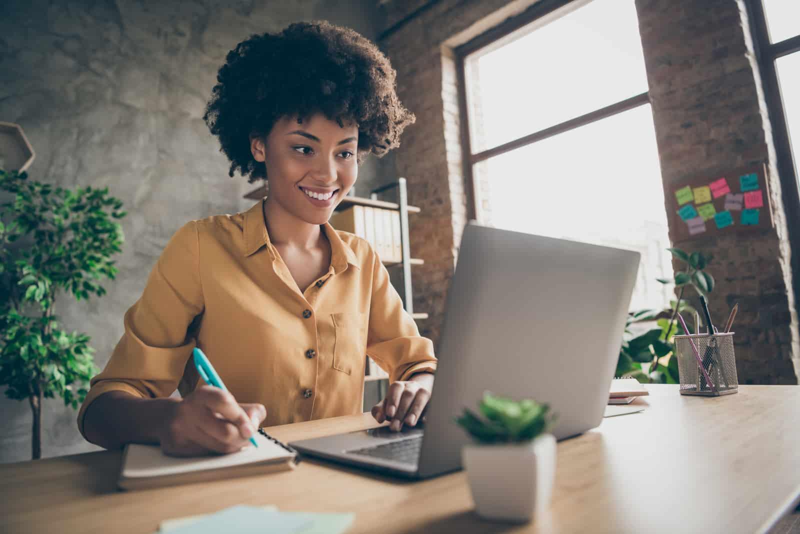 eine lächelnde Frau, die im Büro arbeitet