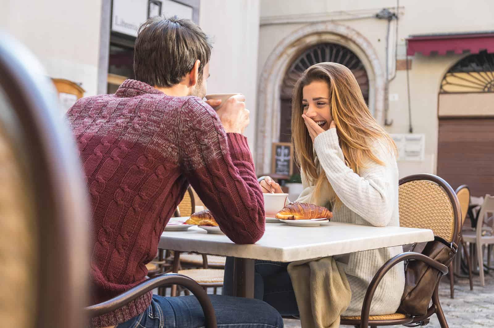 eine lachende Frau, die mit einem Mann im Café sitzt und zusammen frühstückt