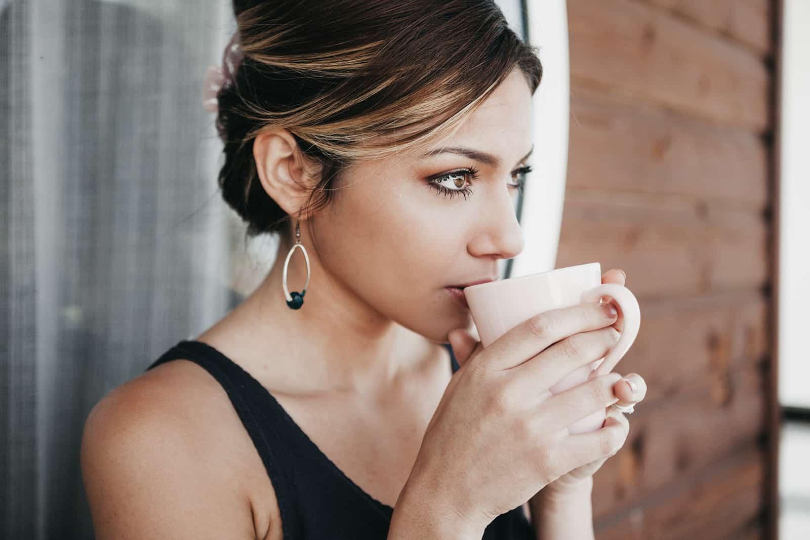 eine nachdenkliche Frau, die auf dem Balkon Kaffee trinkt