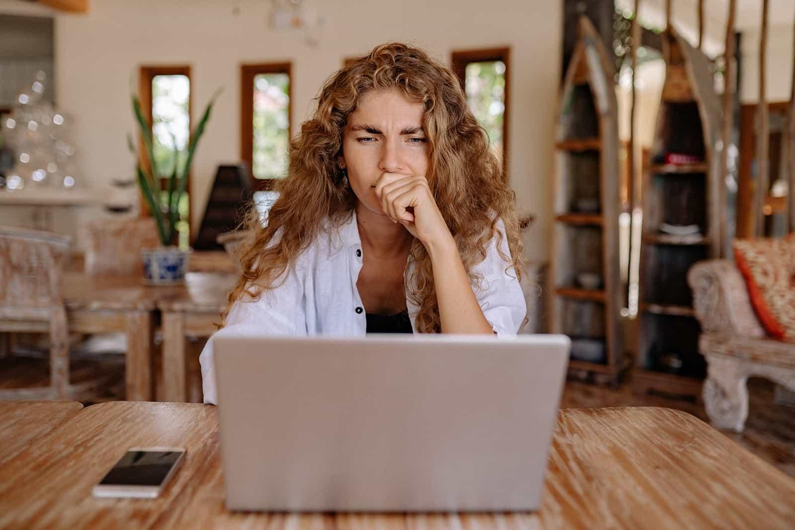 eine nachdenkliche Frau, die Laptop betrachtet, der zu Hause am Tisch sitzt