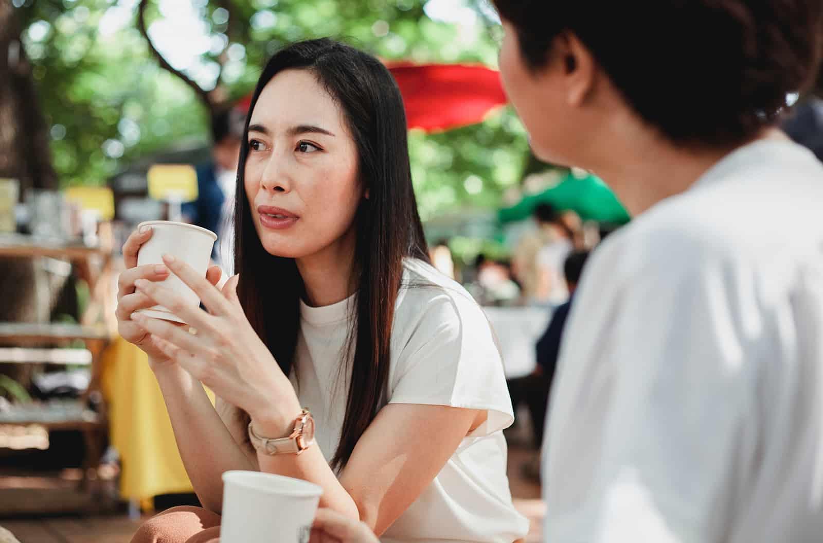 eine nachdenkliche Frau, die beiseite schaut, während sie mit einem Freund draußen im Café sitzt