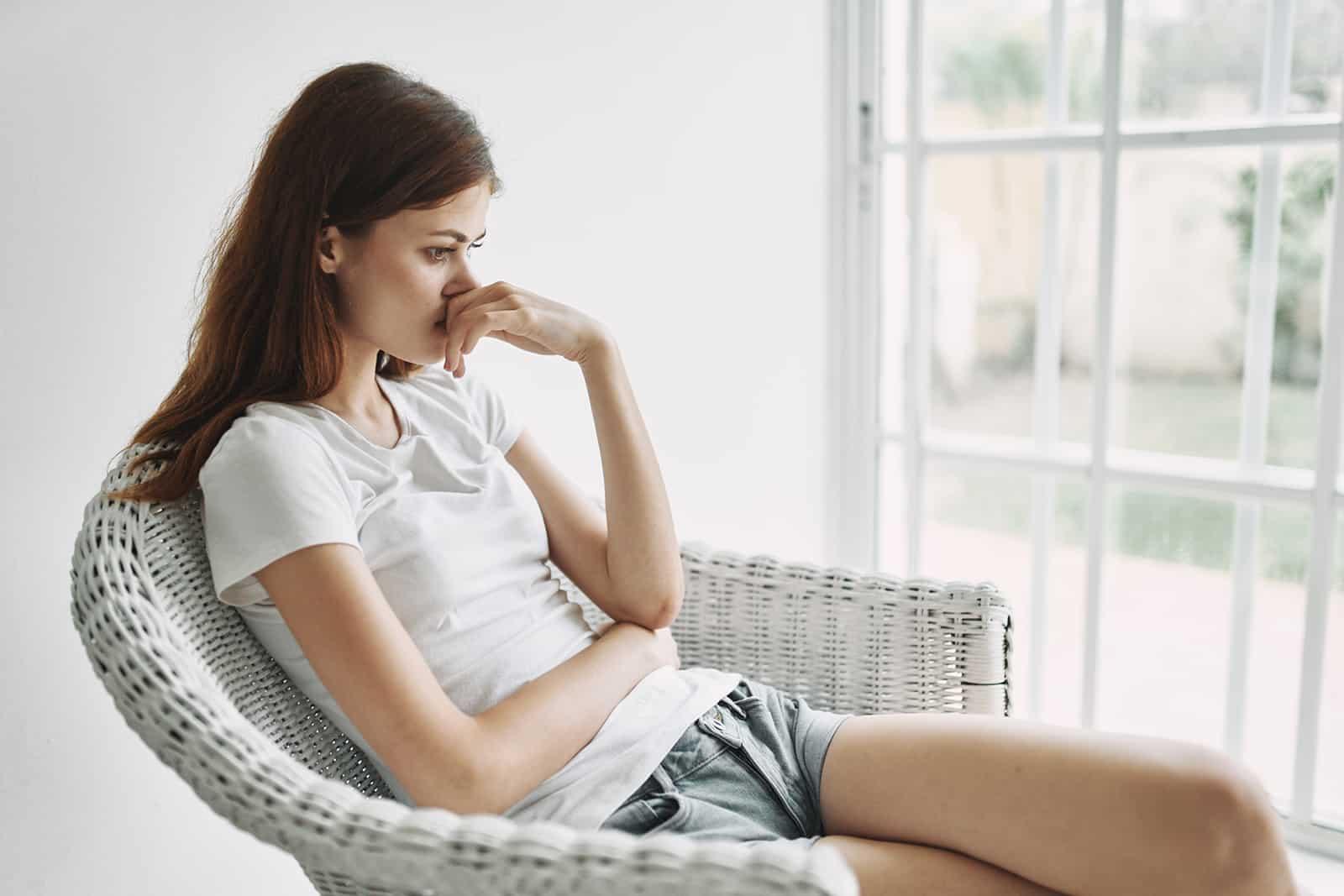 eine nachdenkliche Frau, die im Sessel neben dem Fenster sitzt