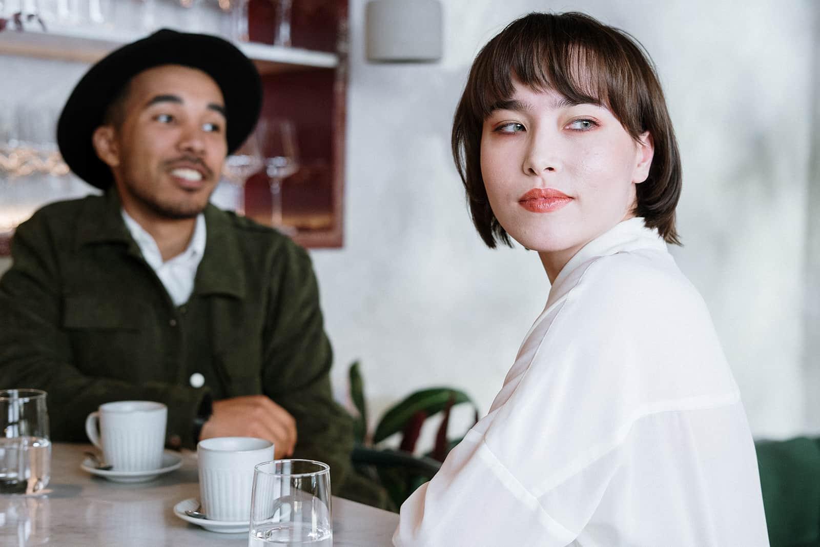 eine nachdenkliche Frau, die mit einem Freund in einem Café sitzt und den Kopf dreht, während er spricht
