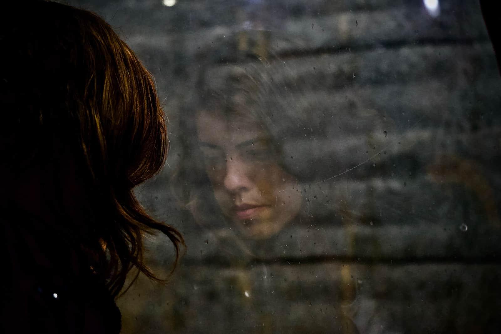eine nachdenkliche Frau, die nach unten schaut und vor dem Fenster steht