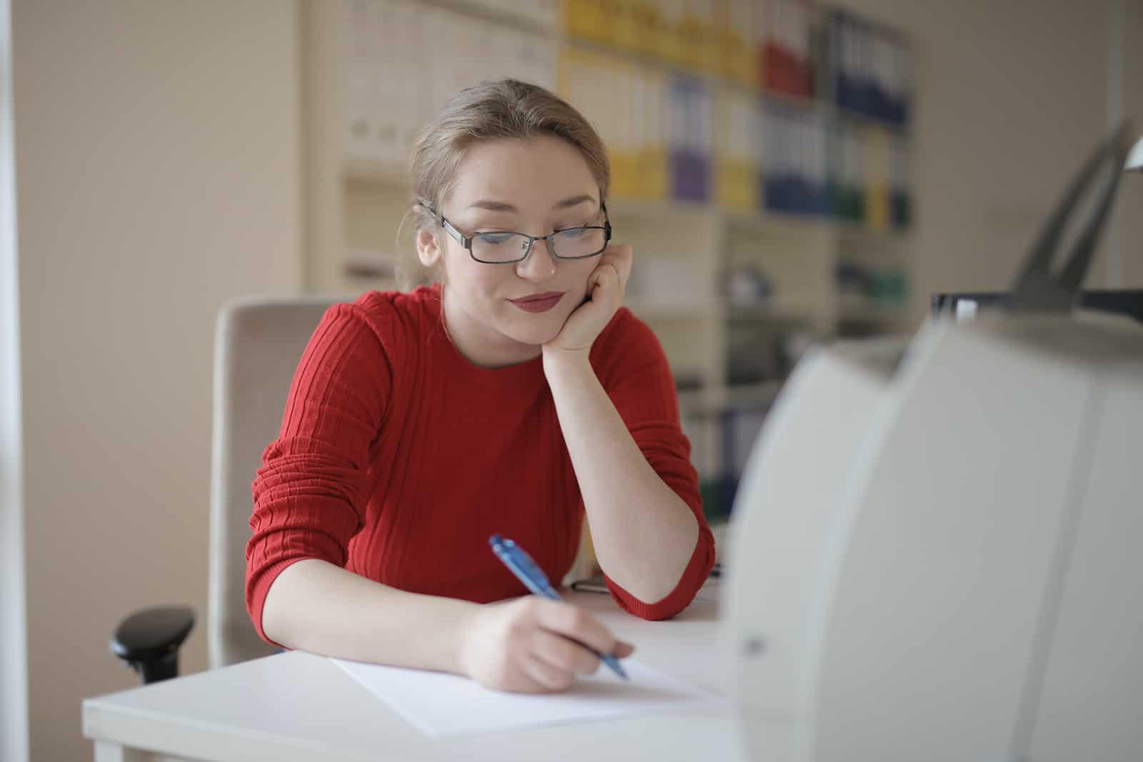 eine nachdenkliche Frau, die einen Stift hält, während sie im Büro sitzt