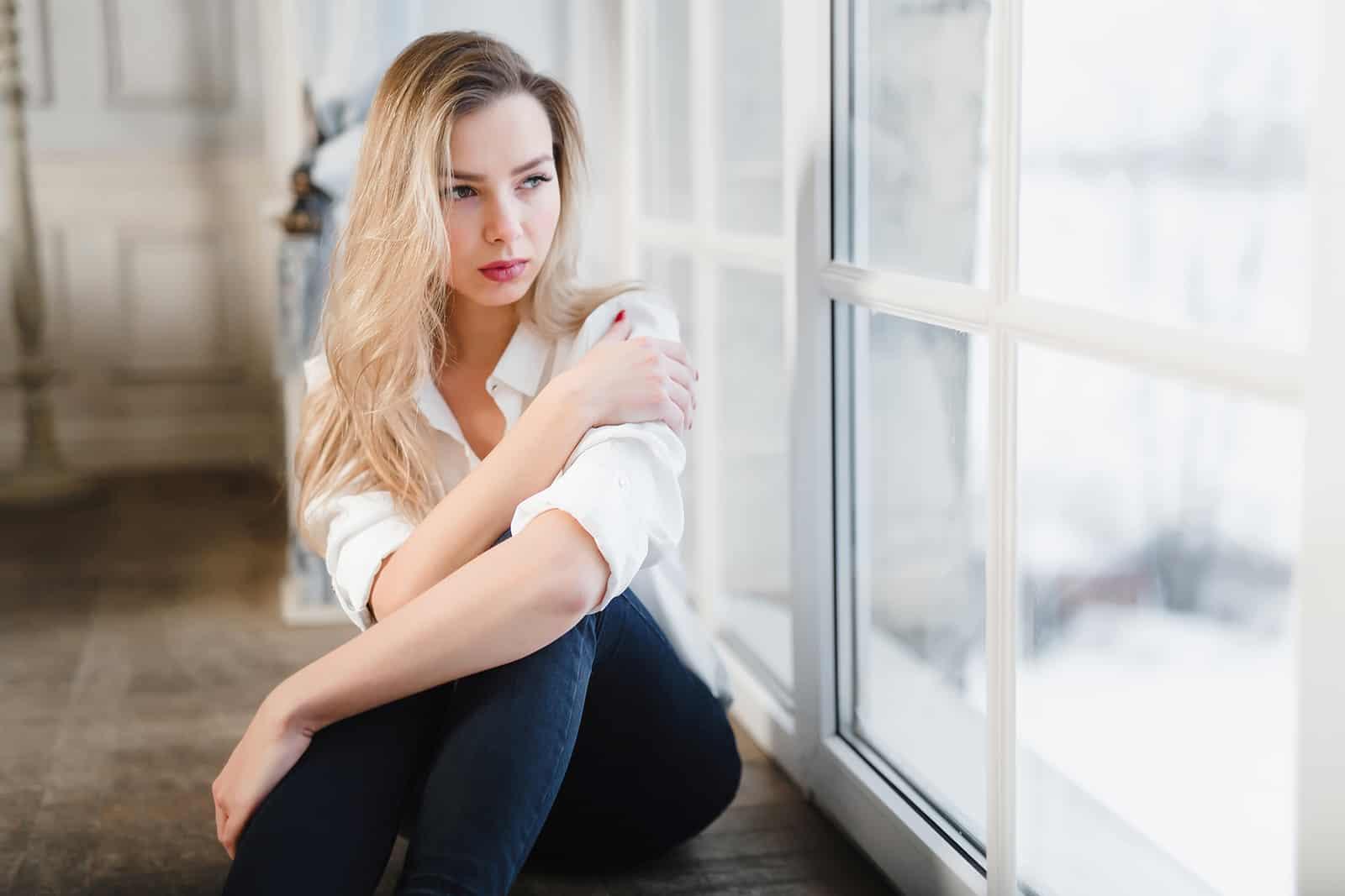 eine nachdenkliche Frau, die auf dem Boden neben den Glastüren sitzt