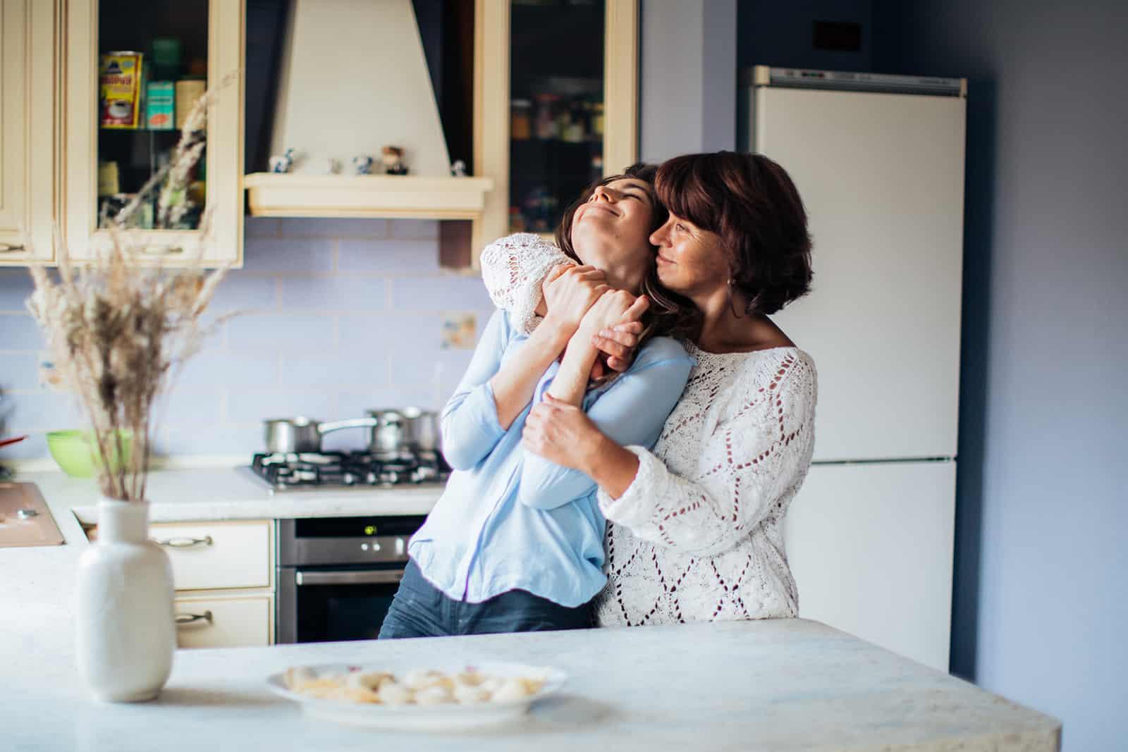 Eine reife Mutter umarmt ihre Tochter und steht in der Küche