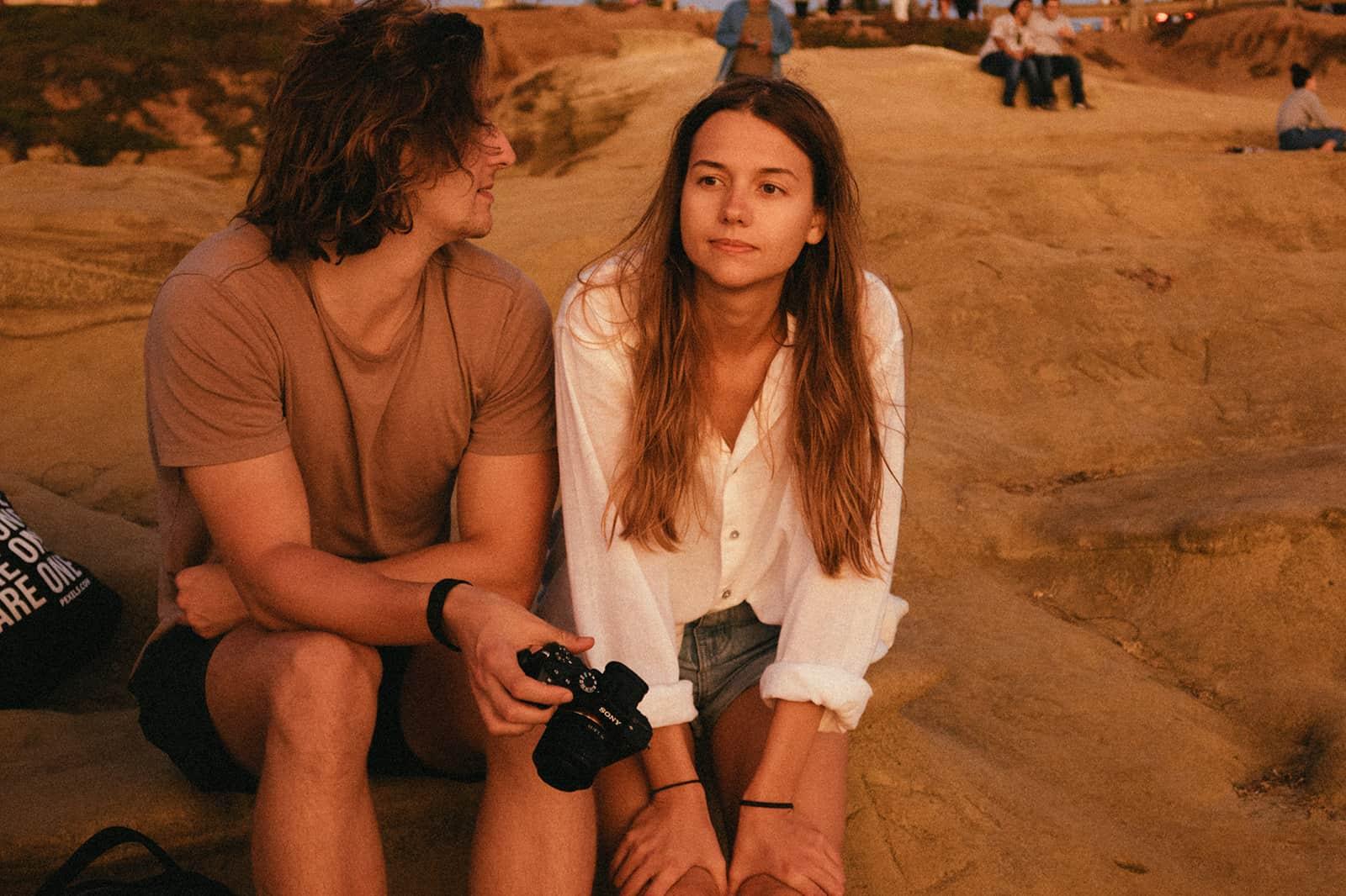 Eine ruhige Frau sitzt auf dem Felsen neben einem Mann, der sie ansieht