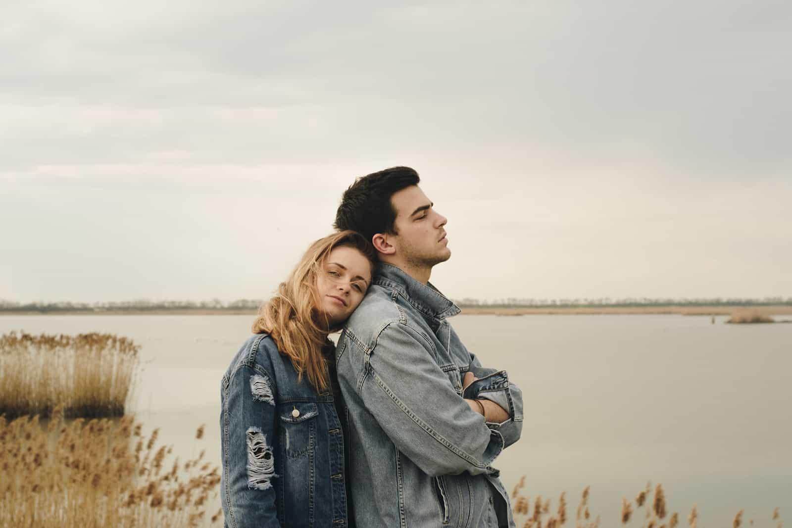 Eine ruhige Frau, die sich auf ihren Freund stützt und ernst aussieht, während sie in der Nähe des Sees steht