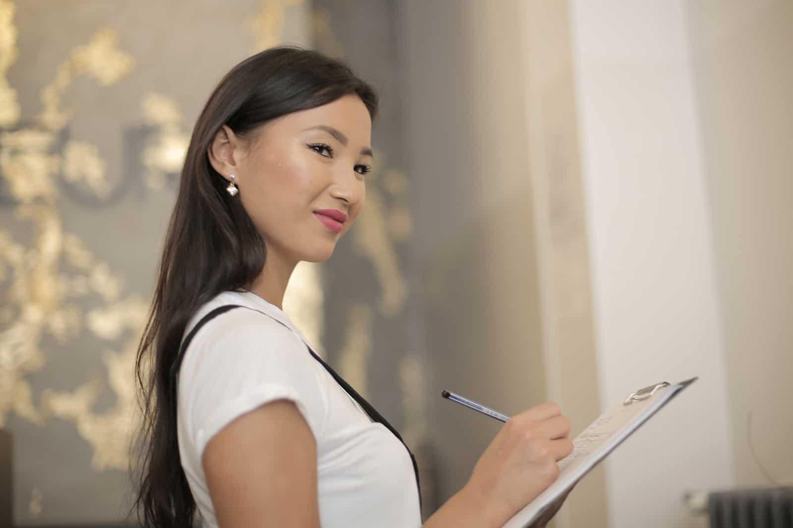 eine schöne Frau mit langen schwarzen Haaren, die eine Checkliste hält