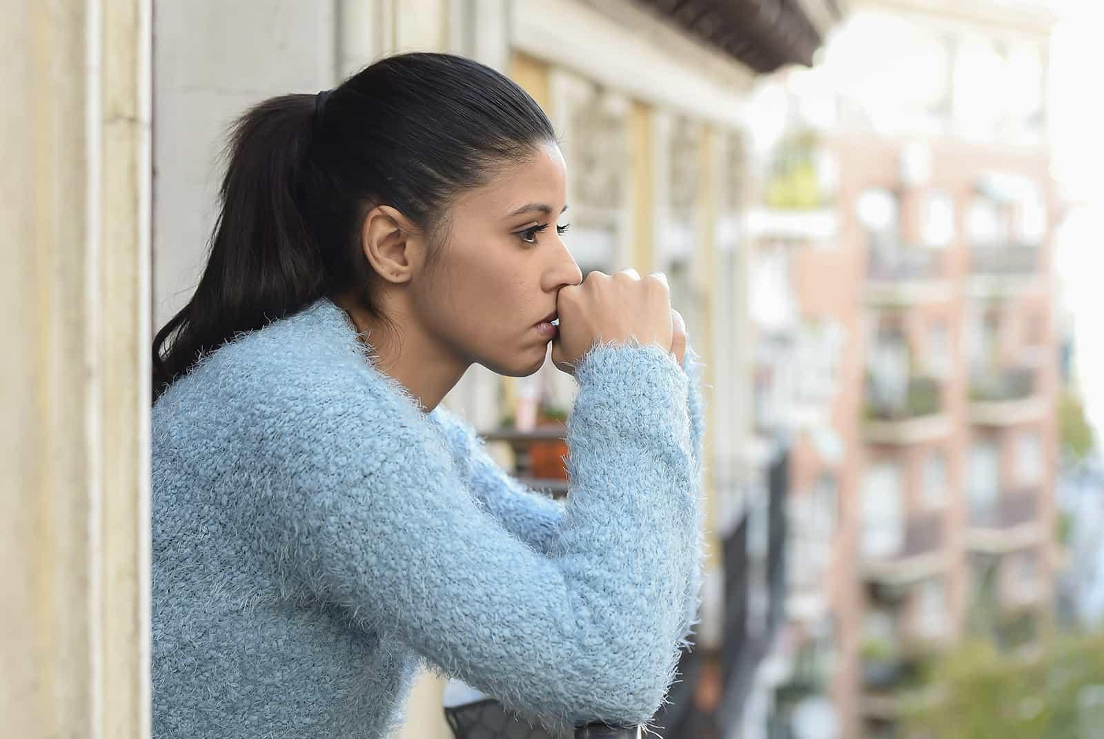 eine traurige Frau, die beim Nachdenken auf dem Balkon steht