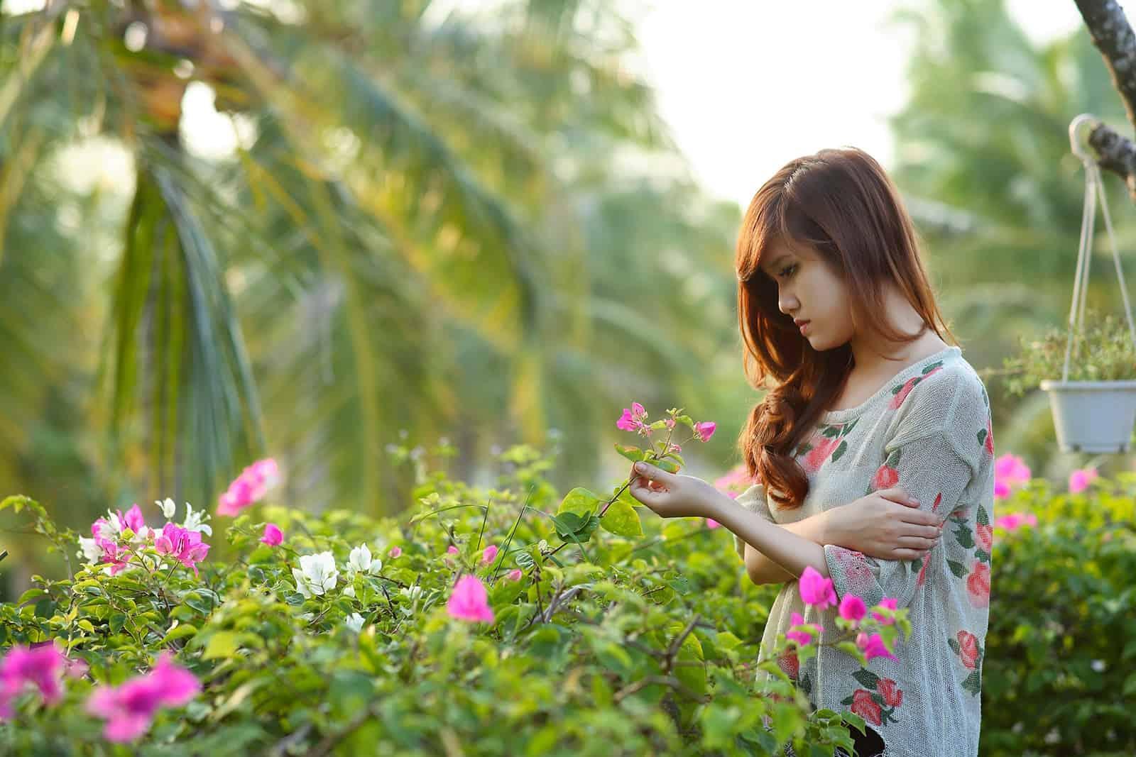 eine traurige Frau, die rosa Blumen berührt, die im Garten stehen