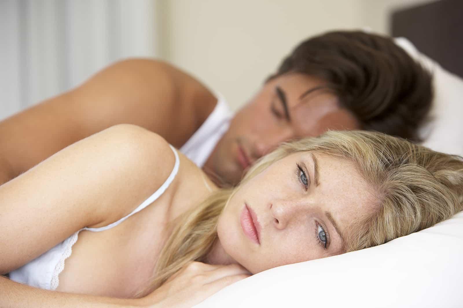 eine traurige Frau, die wach in einem Bett neben einem schlafenden Mann liegt