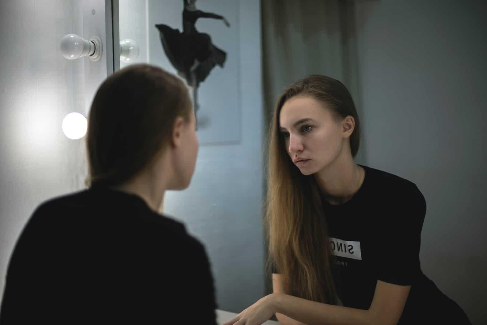 eine traurige Frau in einem schwarzen T-Shirt, die sich in den Spiegel schaut