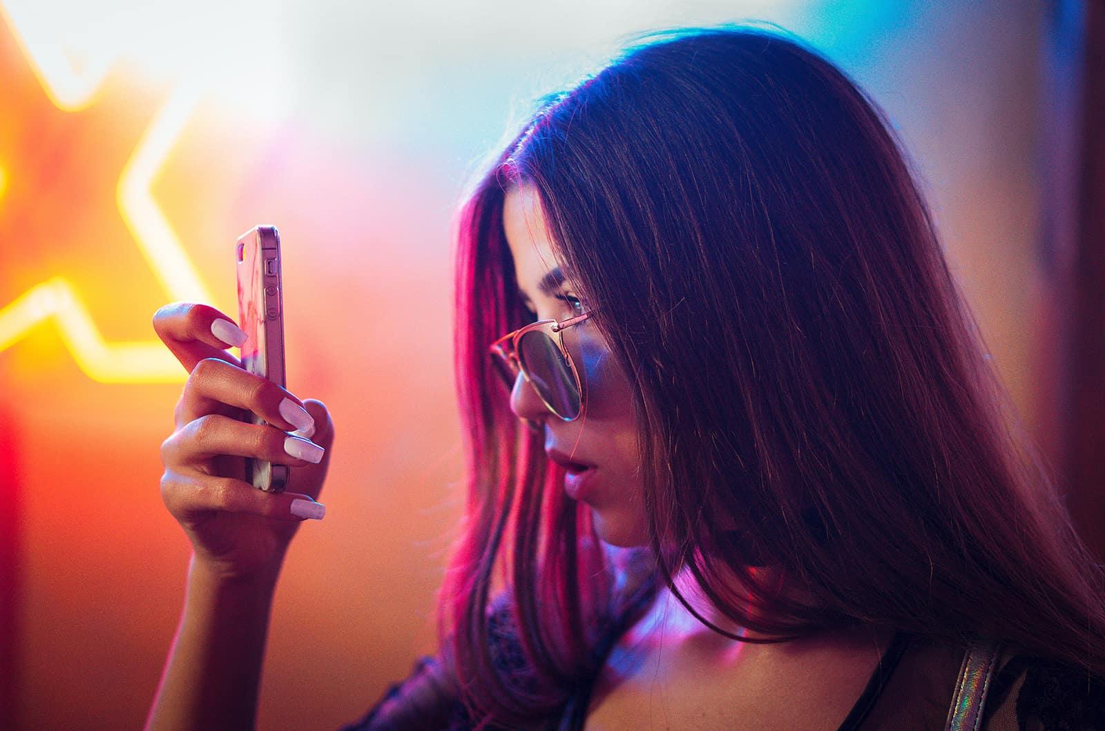 eine überraschte Frau, die ein Smartphone betrachtet, während sie in der Nähe der Neonlichter steht