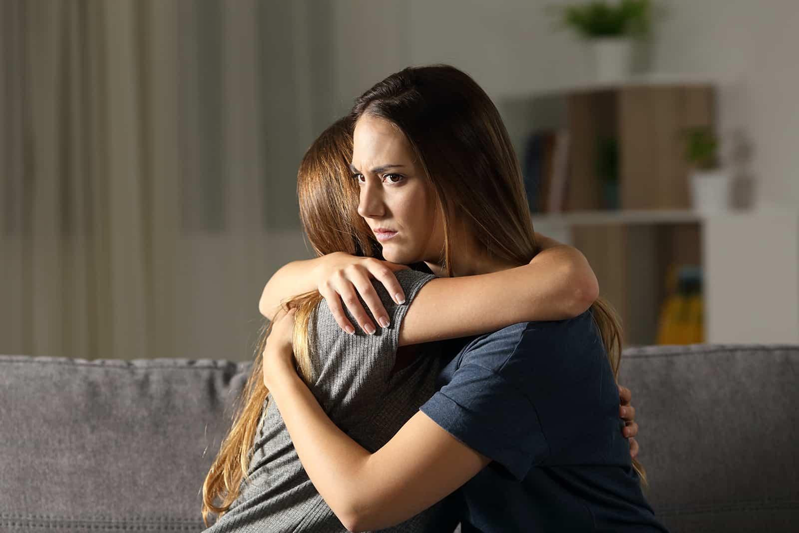 eine verärgerte Frau umarmt eine andere Frau, die auf der Couch sitzt