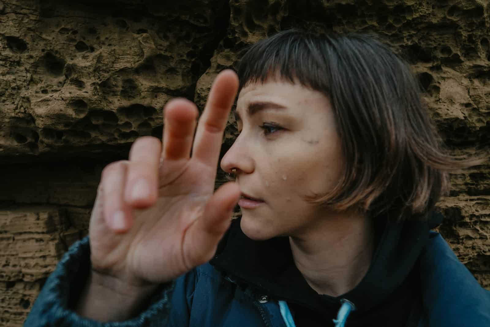 eine weinende Frau, die in der Nähe des Felsens steht und ihre rechte Hand hebt