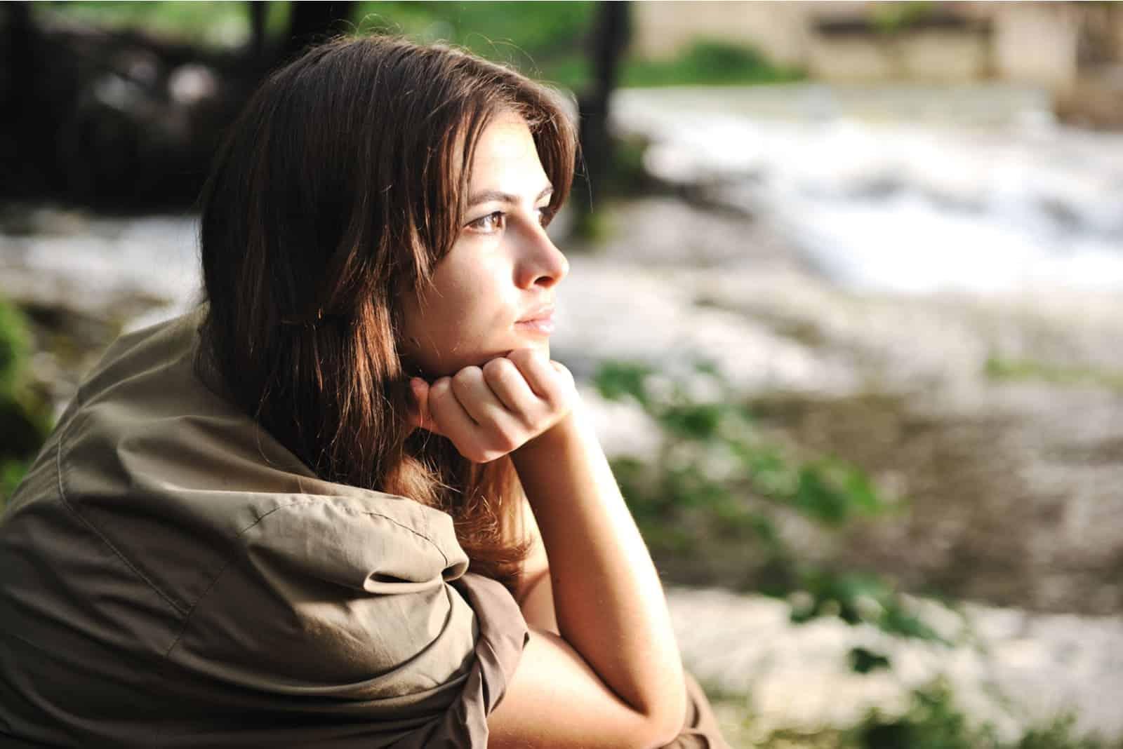 einsame nachdenkliche Frau, die alleine in der Natur sitzt