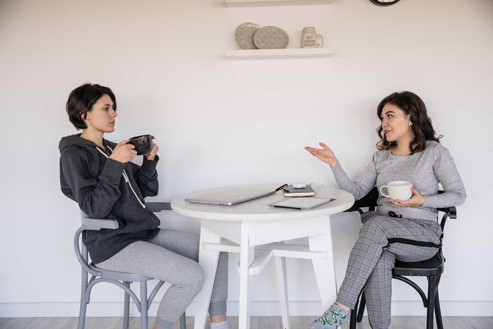 ernsthafte Frau, die einer Freundin zuhört, die mit ihr spricht, während sie zusammen Kaffee trinkt