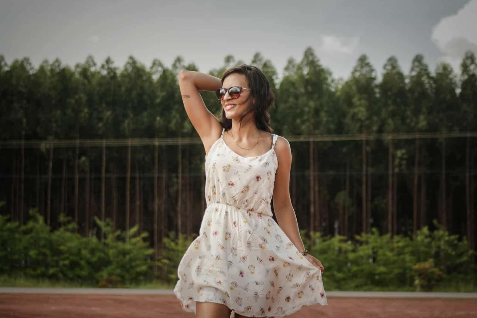 glückliche Frau im weißen Kleid, das ihre Haare berührt