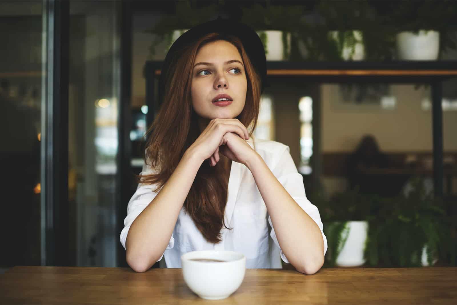 hinter der bar neben dem cafe sitzt und denkt eine schöne frau