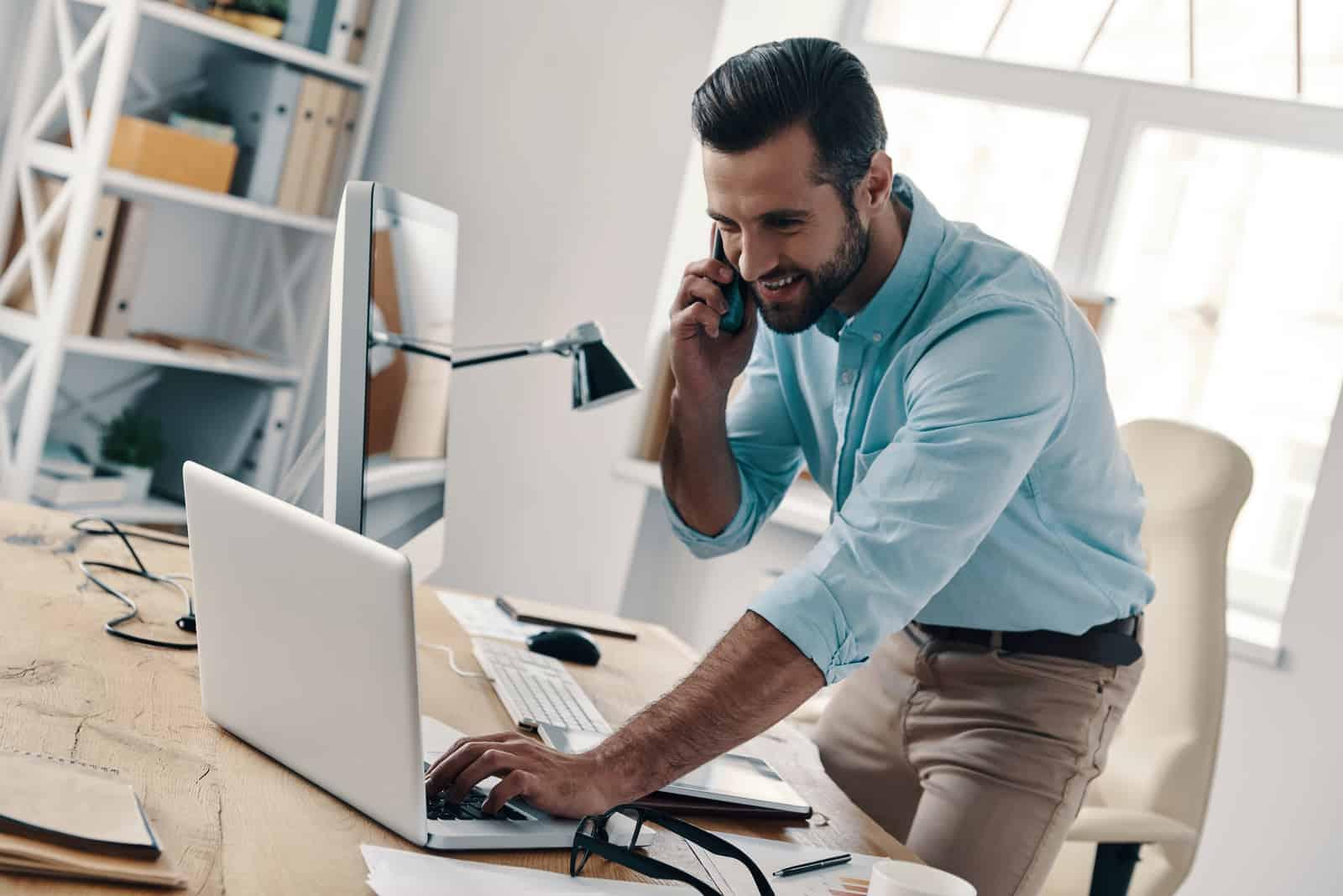 im Büro ein lächelnder Geschäftsmann, der auf einem Handy spricht und einen Laptop benutzt