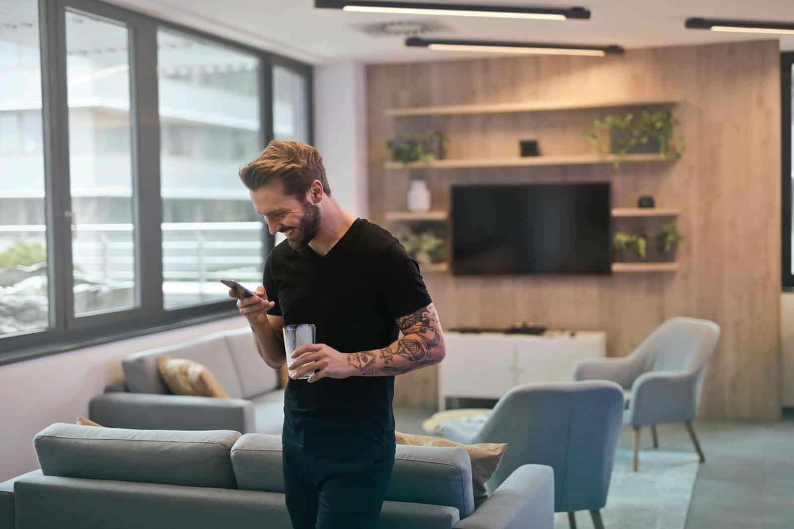 lächelnder Mann, der Smartphone betrachtet, das im Wohnzimmer steht