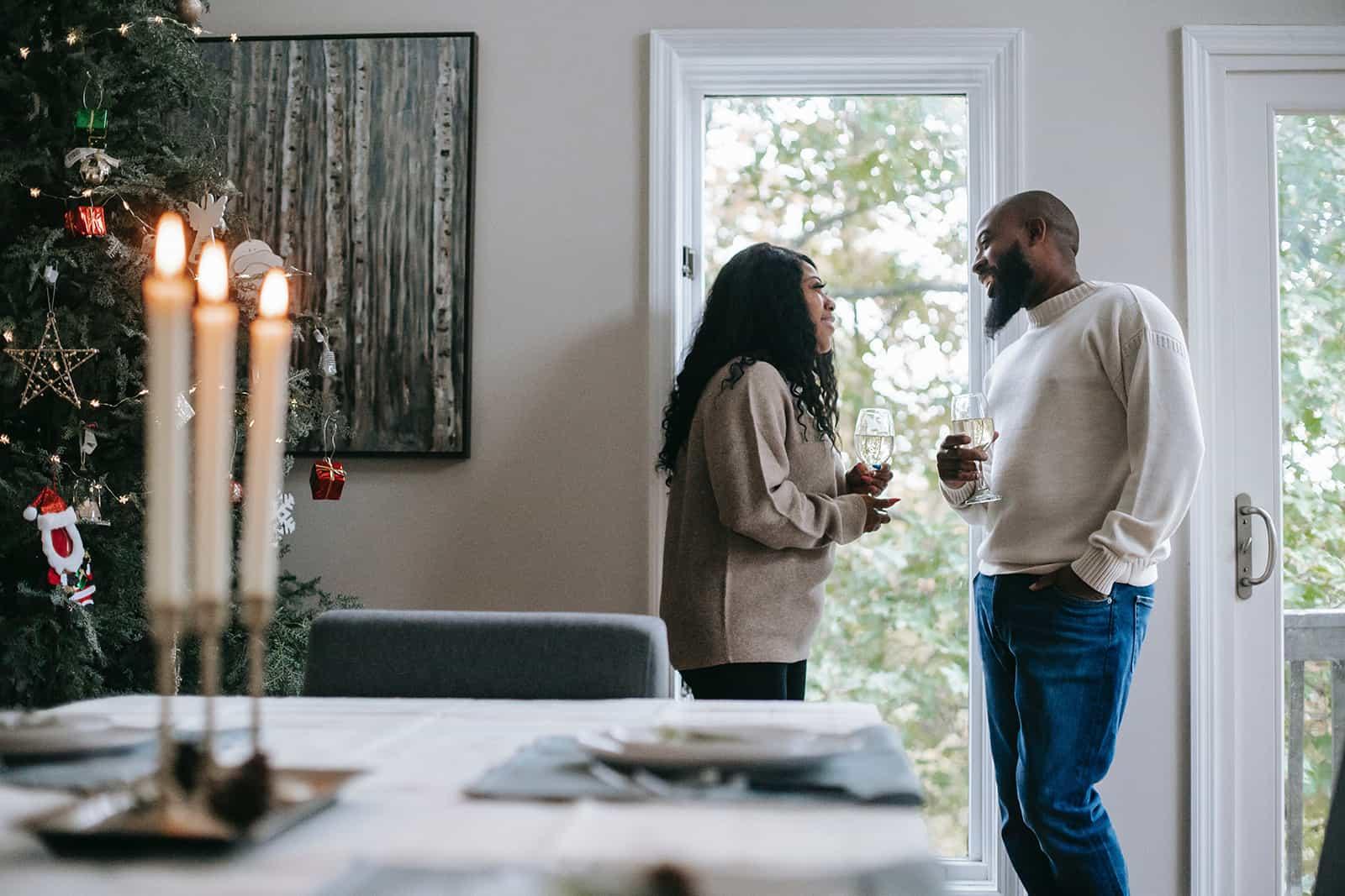 lächelndes Paar, das ein Glas Champagner hält, das nahe am Fenster zu Hause steht