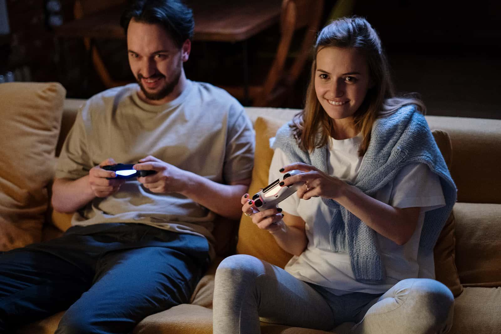 lächelndes Paar, das Konsolen für Videospiele hält, die auf der Couch sitzen