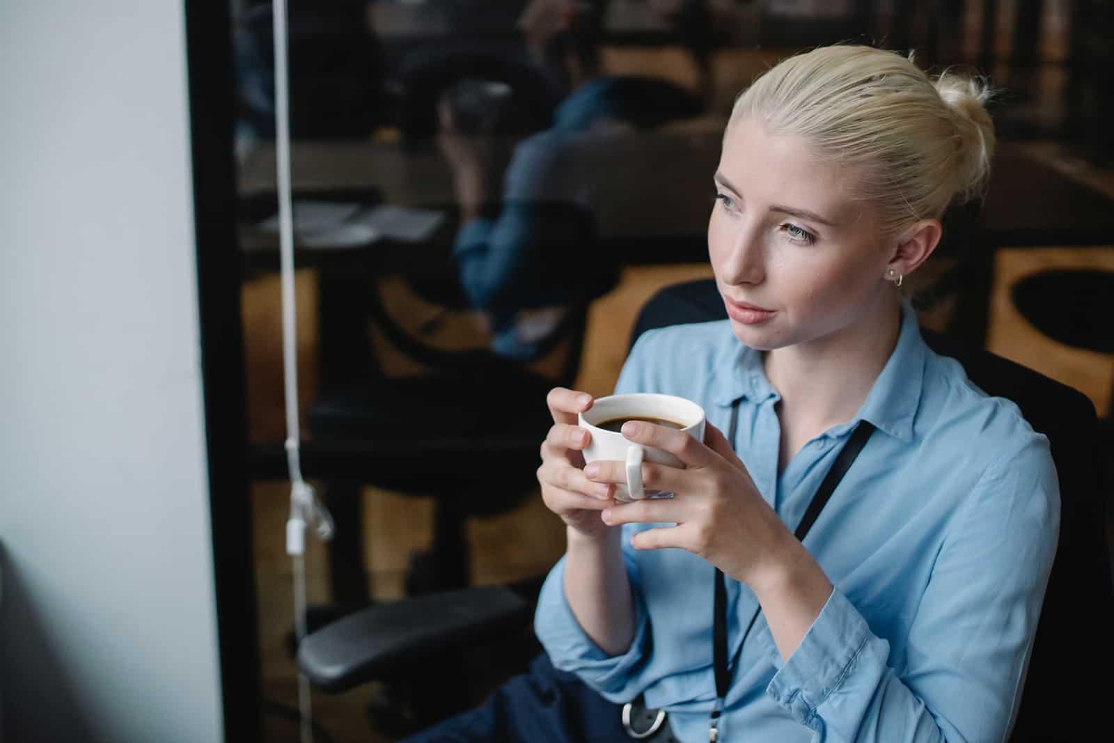 nachdenkliche Frau hält eine Tasse Kaffee im Café sitzen
