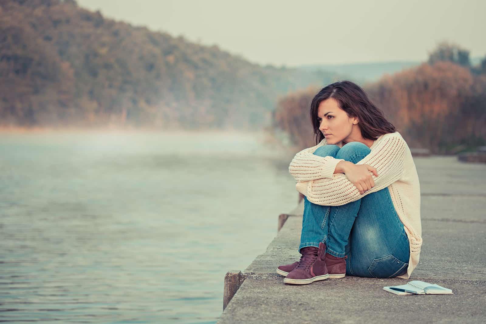 nachdenkliche Frau, die am frühen Morgen in der Nähe des Sees sitzt