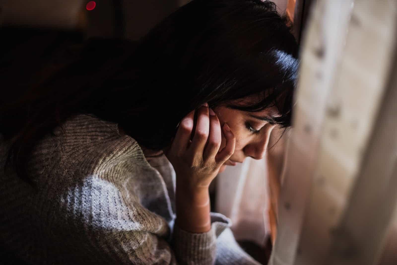 nachdenkliche traurige Frau, die am Fenster sitzt