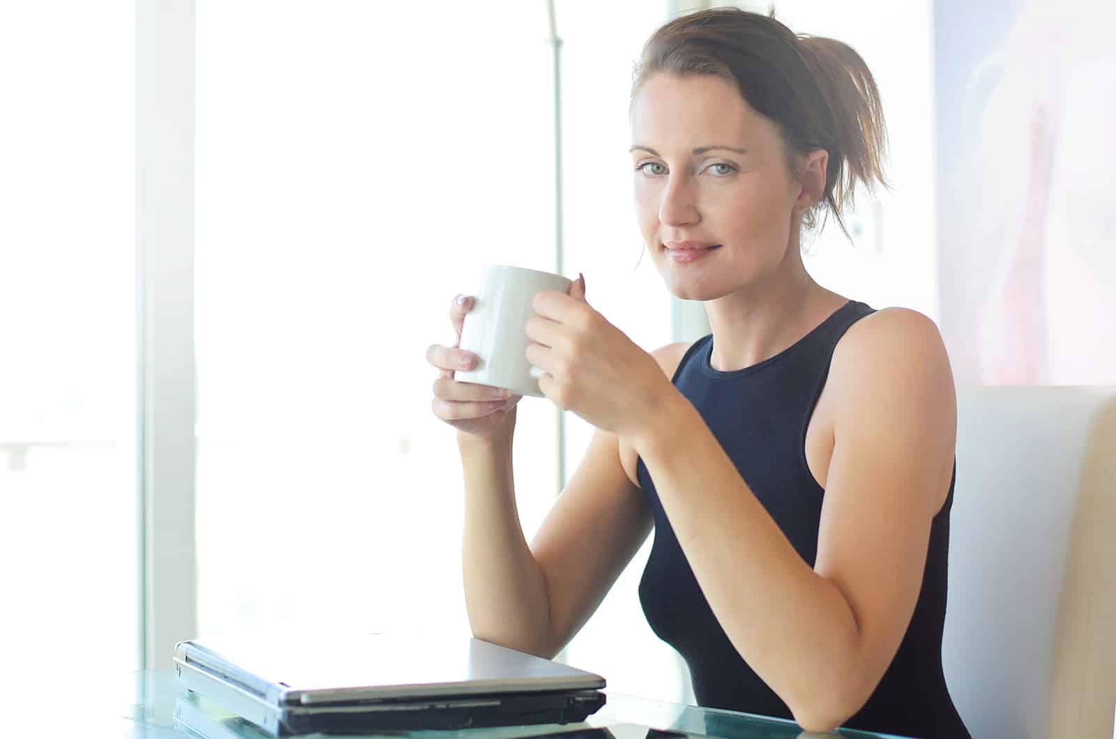 positive Frau, die eine Tasse Kaffee hält, die im Büro sitzt