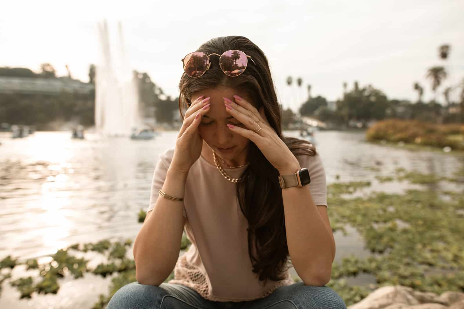 traurige Frau, die ihren Kopf berührt, der allein nahe dem See sitzt