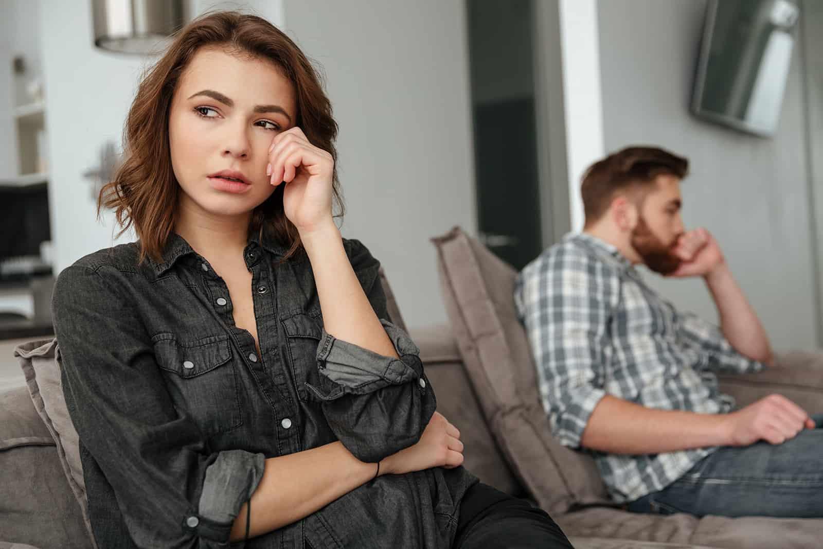 traurige Frau, die auf der Couch sitzt und sich von ihrem Freund abwendet