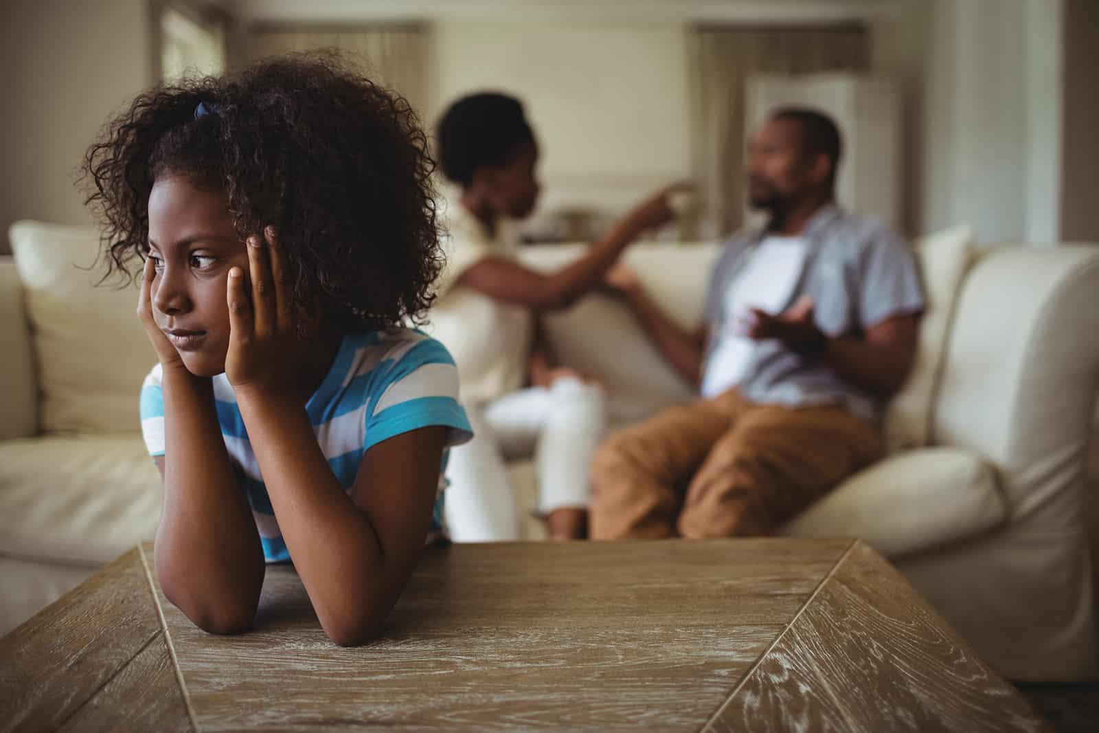 trauriges kleines Mädchen, das sich auf den Tisch lehnt und ihren Eltern beim Streiten zuhört