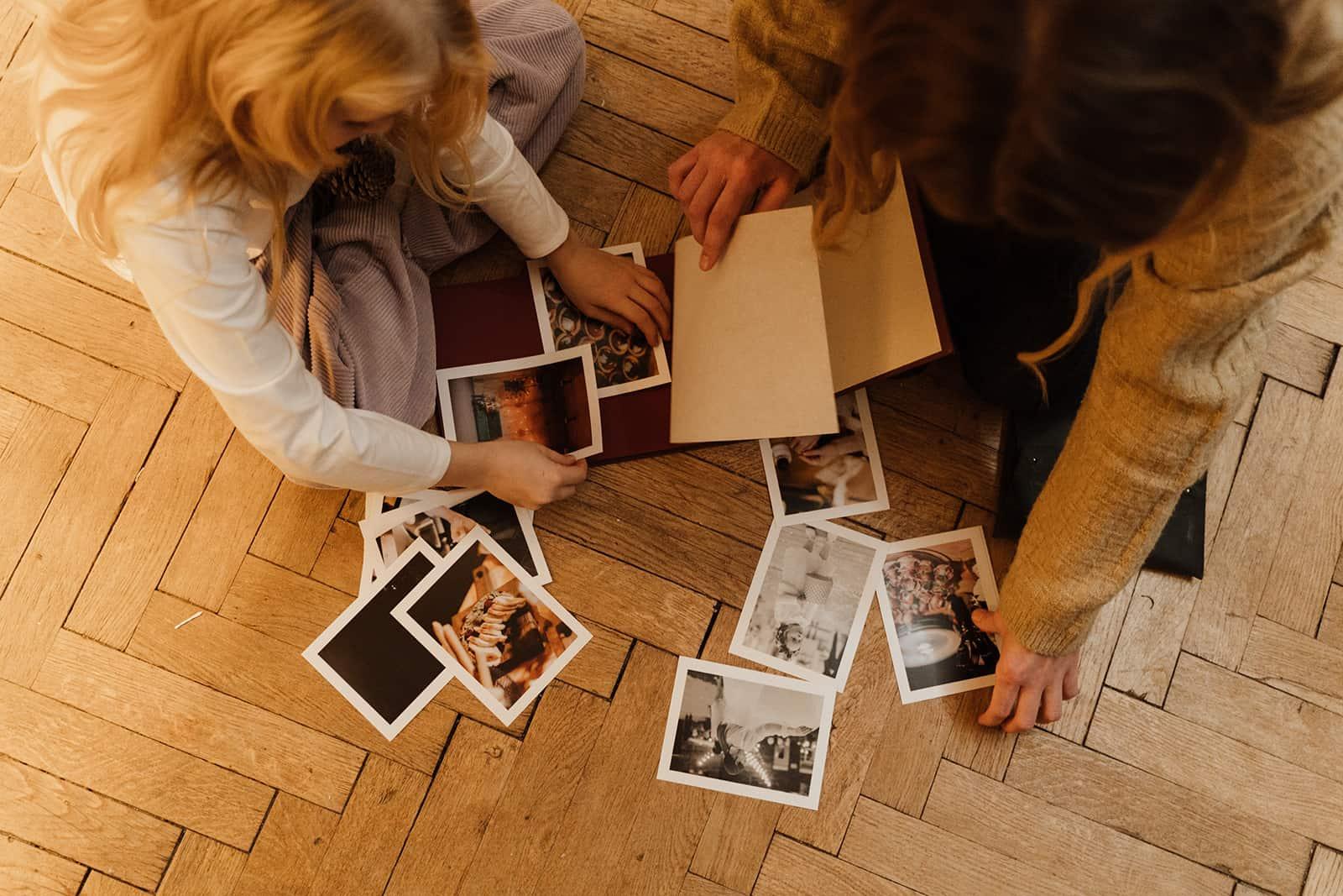 zwei Frauen, die alte Familienfotos betrachten, die auf dem Boden sitzen