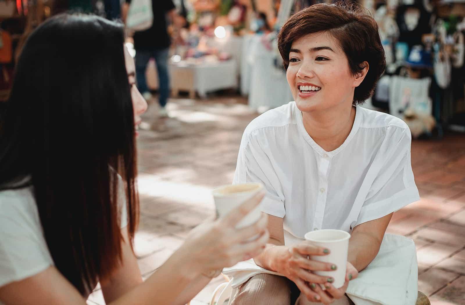 zwei Freundinnen unterhalten sich auf der Straße und trinken zusammen Kaffee